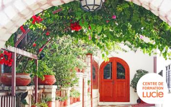 Porte rouge au fond de l'image et une arche remplie de verdure et fleurs en premier plan