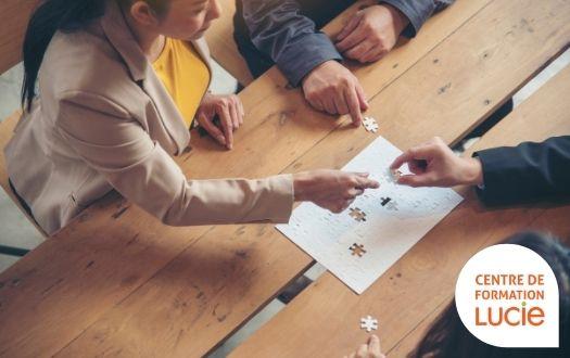 Photo de salariés qui joues au puzzle ensemble sur une table en bois
