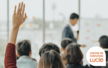 Personne levant la main dans une assemblée - Agence LUCIE